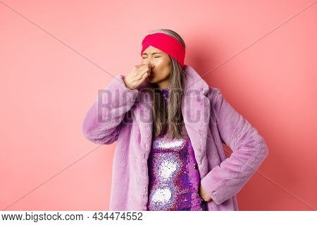 Portrait Of Stylish Old Asian Woman In Fashionable Purple Coat And Dress, Shut Nose From Bad Smell,