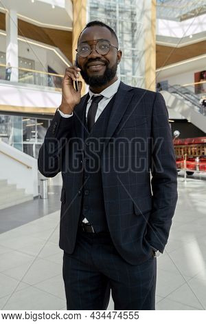 Young well-dressed man of African ethnicity talking on mobile phone in front of camera