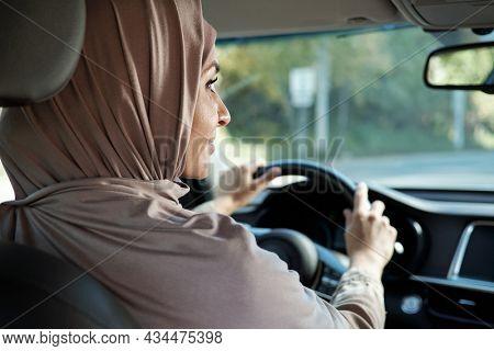 Horizontal rear view portrait shot of modern Muslim woman wearing hijab driving car looking into side-view mirror