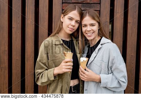 Two pretty teenage girls with icecream cones standing against building exterior
