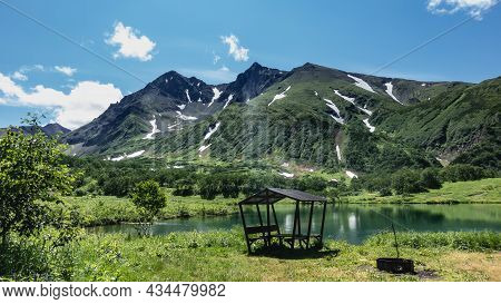 There Is A Picturesque Lake In The Valley. On The Shore There Is A Canopy And A Barbecue. A Mountain