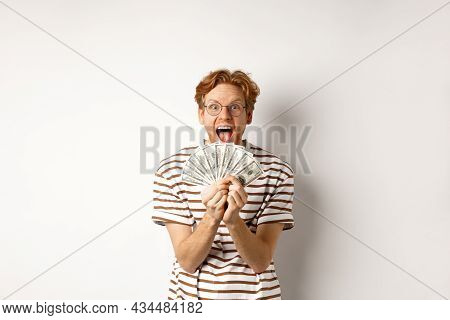 Lucky Young Man With Red Hair Showing Dollars, Winning Money And Screaming Of Happiness, Holding Pri