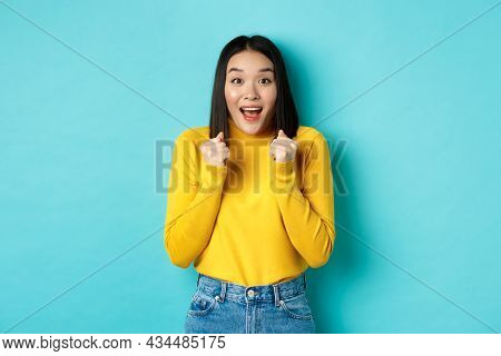 Hopeful And Happy Asian Woman Looking With Amazement And Hope At Camera, Winning, Standing Over Blue