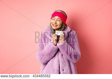 Shopping And Fashion Concept. Fashionable Asian Woman In Purple Faux Fur Coat, Looking Happy And Sho