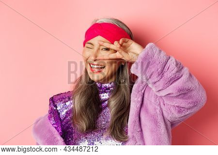 Fashion. Close-up Of Fashionable Asian Senior Woman Smiling, Showing Victory Sign Over Eye And Looki