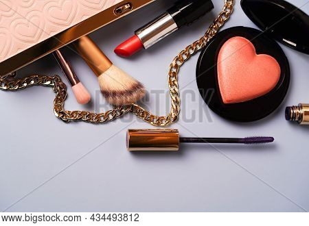 Stylish Pink Handbag With Makeup Accessories: Lipstick, Mascara, Blush On A Colored Background