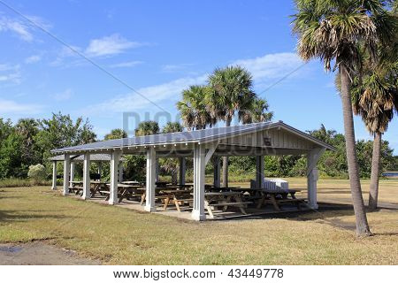 A dozen wood picnic tables covered by an open building in Hugh Taylor Birch State park in Fort Lauderdale Florida surrounded by grass palm and other trees and plants on a sunny autumn day. poster