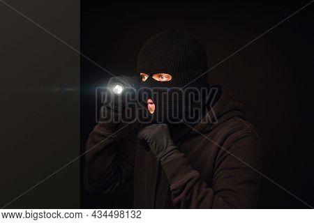 Masked burglar with flashlight on dark back