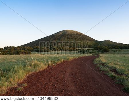 A Low Angle View Of A Red Dirt And Gravel Road Leading To Capulin Volcano National Monument With Pra