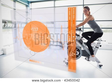 Young attractive girl doing exercise bike with futuristic interface showing calories