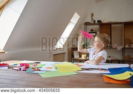 Little boy makes paper plane, kid in workshop