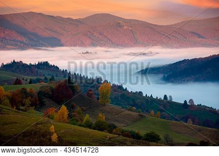Mountain Landscape In Autumn At Sunrise. View From The Top Of A Hill In To The Distant Valley Full O