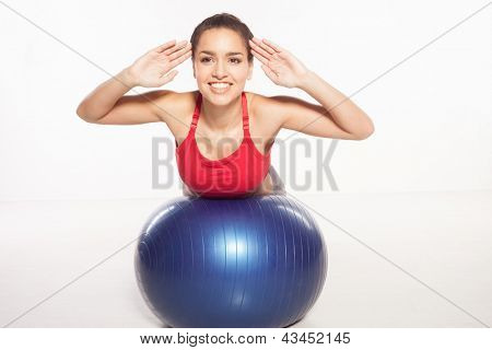 Happy smiling young woman exercising her abs on a pilates ball lying stretched out over the top with her hands raised looking at the camera, isolated studio portrait