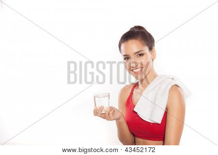 Athletic young woman with a lovely smile standing holding a glass of water with a towel slung over her shoulder isolated on white