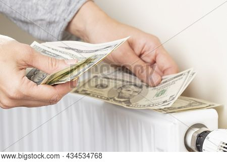 Womans Hand Counting Us Dollars Banknotes And Place On Heating Radiator Battery With Temperature Reg