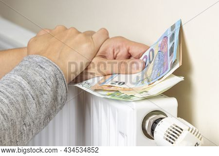 Woman Holding His Hand With Euro Banknotes On Heating Radiator At Home. Family Pay All Money For Hom