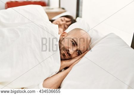 Young hispanic couple sleeping on the bed at bedroom.