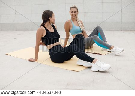 Two Young Pretty Women In Sports Clothes In A Light Gray Gym Of A Fitness Center Are Warming Up And