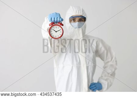 Woman In Protective Medical Suit And Mask With Glasses Holds Red Alarm Clock On White Background