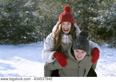 Guy Carries His Girlfriend On His Back. Winter Forest Background. Young Couple Having Fun On Frosty