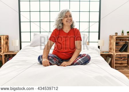Middle age woman with grey hair sitting on the bed at home winking looking at the camera with sexy expression, cheerful and happy face.