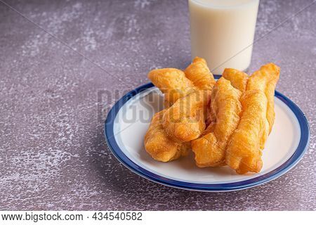Side View Of Deep-fried Dough Sticks Or Chinese Doughnut Sticks On White Plate And A Glass Of Soybea