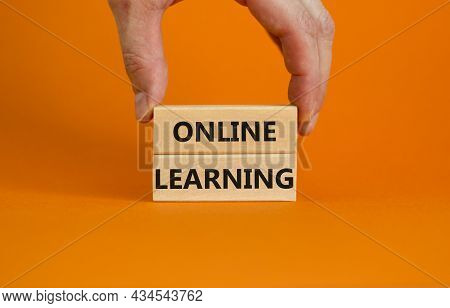 Online Learning Symbol. Concept Words 'online Learning' On Wooden Blocks On A Beautiful Orange Backg