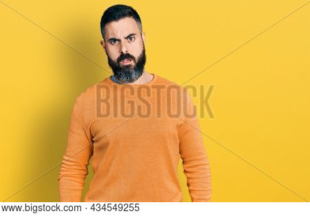 Hispanic man with beard wearing casual winter sweater in shock face, looking skeptical and sarcastic, surprised with open mouth