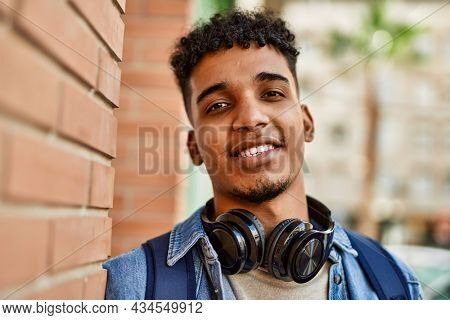Hispanic young man smiling wearing headphones leaning on bricks wall