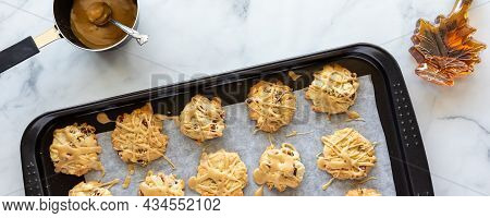 Narrow View Of A Baking Sheet Of Maple Pecan Cookies Drizzled With Maple Icing, Fresh Out Of The Ove