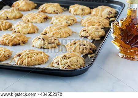A Baking Sheet Full Of Maple Pecan Cookies Fresh Out Of The Oven With A Bottle Of Maple Syrup On The