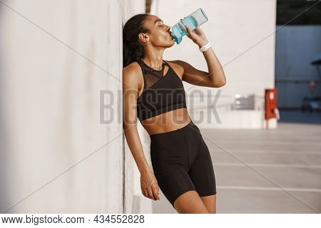Black sportswoman drinking water while leaning on concrete wall outdoors