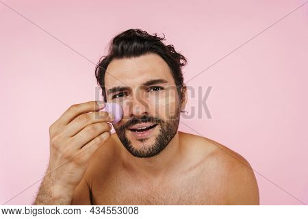 White shirtless man applying concealer with sponge isolated over pink background