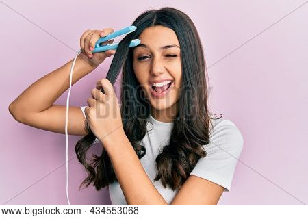 Young hispanic woman holding hair straightener winking looking at the camera with sexy expression, cheerful and happy face.