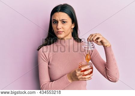 Young hispanic woman holding honey skeptic and nervous, frowning upset because of problem. negative person.