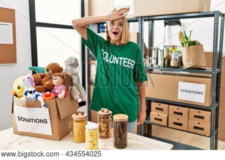 Young caucasian woman wearing volunteer t shirt at donations stand surprised with hand on head for mistake, remember error. forgot, bad memory concept.
