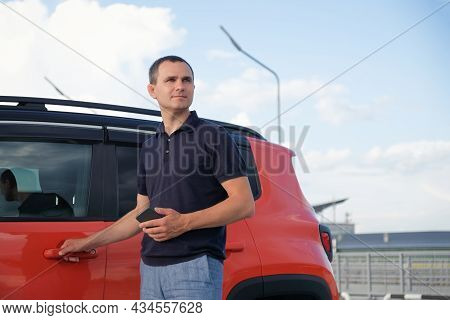 Young Man Stands Near The Car With A Smartphone In His Hands Outdoors