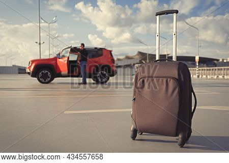 Suitcase In An Open Parking Lot Against The Background Of A Car Close-up