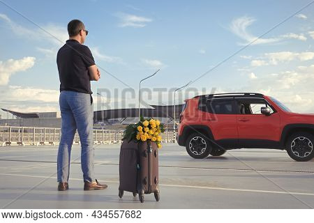 Young Businessman With Luggage And Flowers In An Open Parking Lot Waiting For A Passenger.
