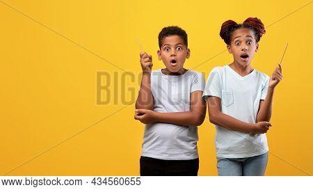 Excited Black Siblings Showing Eureka Gesture On Yellow