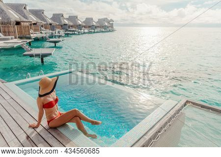 Luxury travel vacation in Bora Bora high end resort hotel tourist lady tanning in bikini by the swimming pool at overwater villa suite.