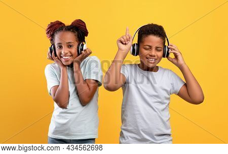 Emotional Black Siblings With Wireless Headsets Listening To Music