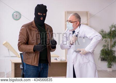 Masked man burglar bribing old doctor for getting vaccine