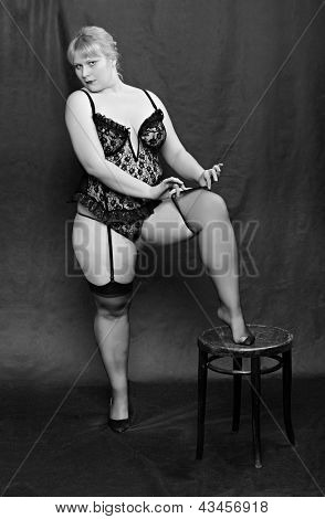 Vintage style picture of an seductive woman dressed in black lingerie posing on a black background.