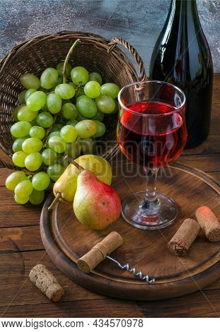 Glass Of Red Wine, Bunch Of Grapes, Fruits And Corkscrew On Wooden Table.
