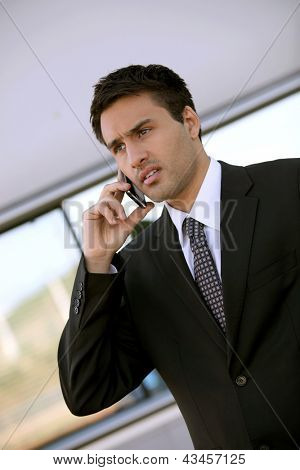 Concerned businessman holding cellphone
