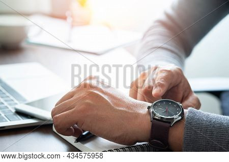 Close-up Image Of Fashion Luxury Brown Watch On Wrist Of Man. Businessman Working With Laptop On Des