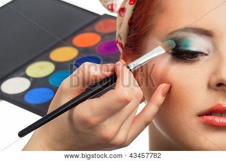 Backstage scene: Professional Make-up artist doing pinup model makeup at work