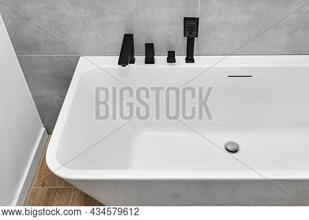 A Modern, Free Standing Wall Mounted Bathtub With A Black Matt Tap, Standing In A Bathroom Lined Wit