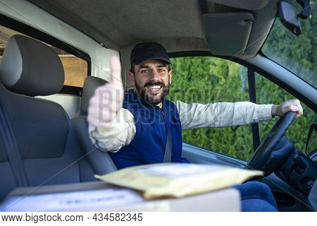 Fast Delivery Service And Professional Deliveryman In His Van Holding Thumbs Up.